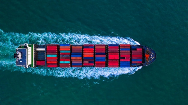 Container freight ship carrying container box for import and export business logistic and transportation by container ship in open sea, aerial view. Premium Photo