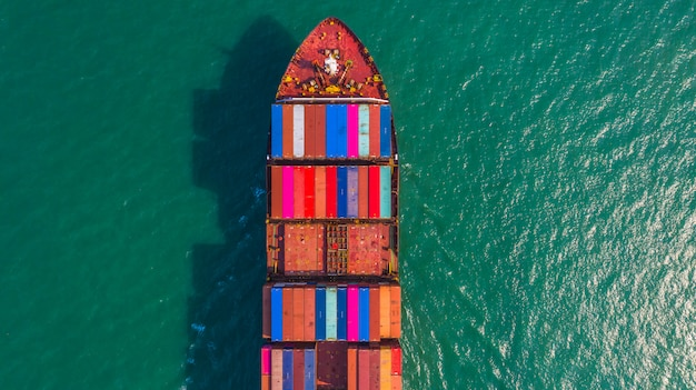 Container ship going to deep sea port, business logistic import export shipping and transportation by container ship, aerial view. Premium Photo