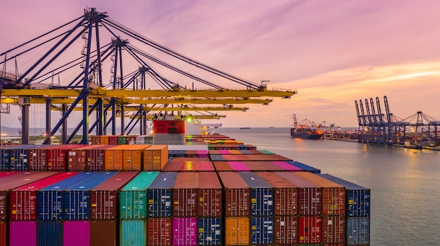 Container ship loading and unloading in deep sea port at sunset, aerial view of business logistic im