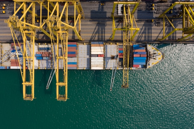 Container ship terminal, and quay crane of container ship at industrial port with shipping container vessel Premium Photo