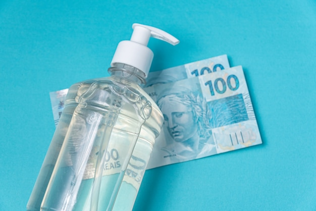 Container with gel alcohol and brazilian real money, Free Photo