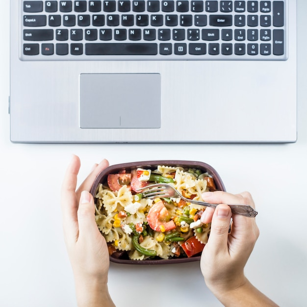 Container with salad with pasta in the workplace near the computer Premium Photo
