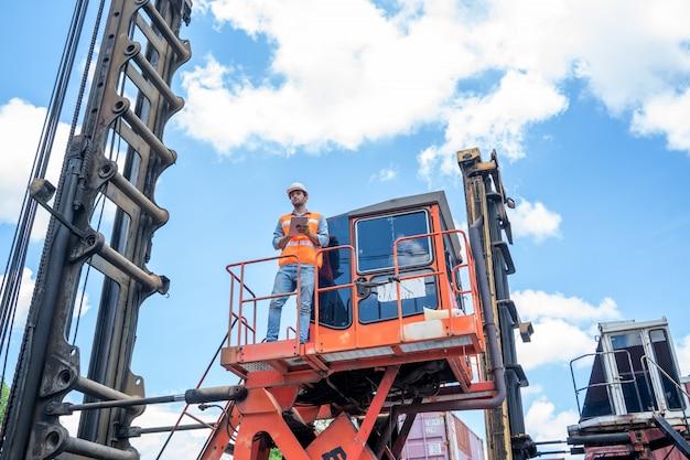 Работник контейнеровоза работает и проверяет на складе контейнеров. Premium Фотографии