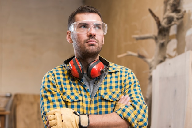 Contemplated male carpenter wearing safety glasses standing with her arms crossed Free Photo