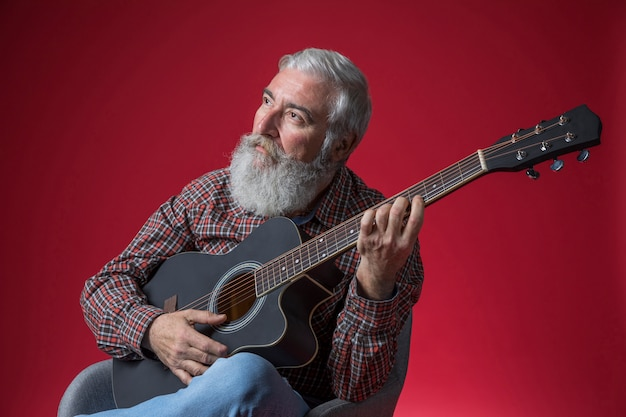 Contemplated senior man playing guitar against red background Free Photo