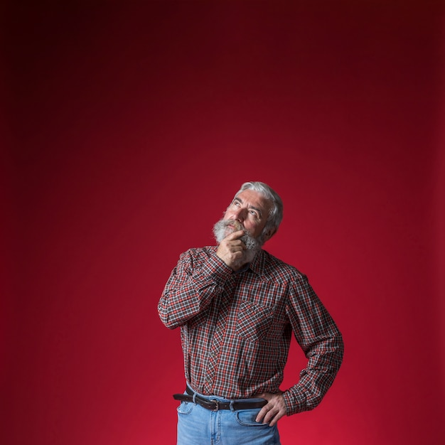 Contemplated senior man with hand on his chin looking up against red backdrop Free Photo