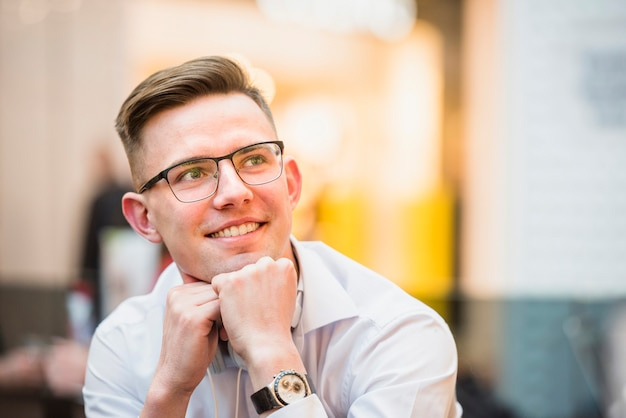 Contemplated smiling young man wearing eyeglasses with chin on his head Free Photo