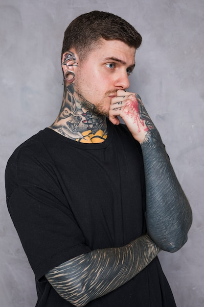 Contemplated tattooed young man with piercing in his ear standing against grey wall Free Photo