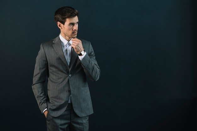 Contemplated young businessman against black background Free Photo