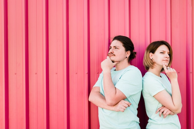 Contemplated young couple standing against red iron wall Free Photo