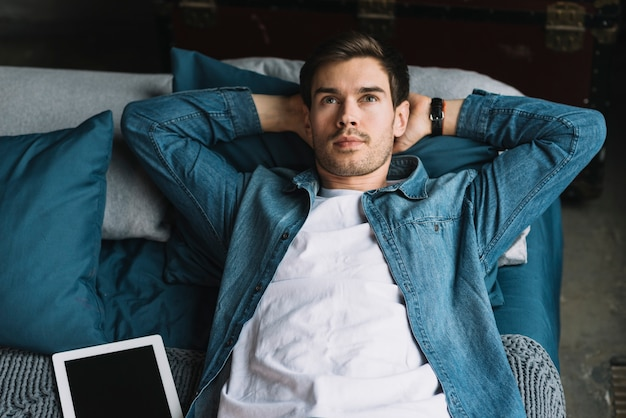 Contemplated young man lying on bed looking up with digital tablet Free Photo