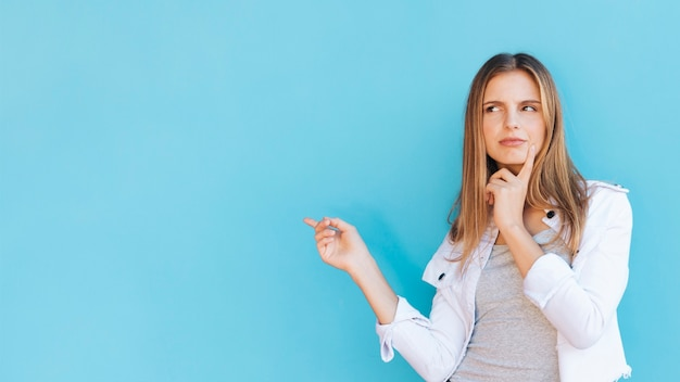 Contemplated young woman pointing finger against blue background Free Photo