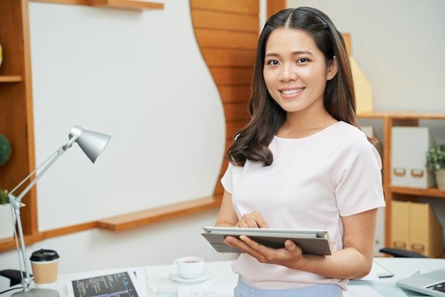 Contemporary businesswoman with tablet smiling at camera Free Photo