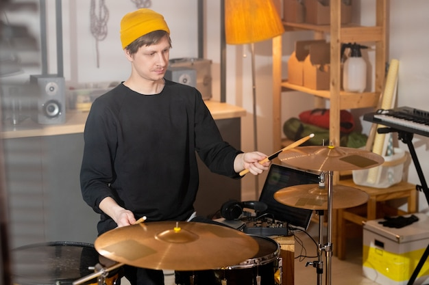 차고에서 드럼 키트로 리허설하면서 나무 나지만으로 심벌즈를 치는 캐주얼웨어를 입은 현대 음악가 프리미엄 사진