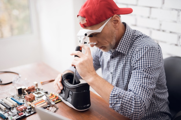 Contemporary senior fixes virtual reality glasses. Premium Photo