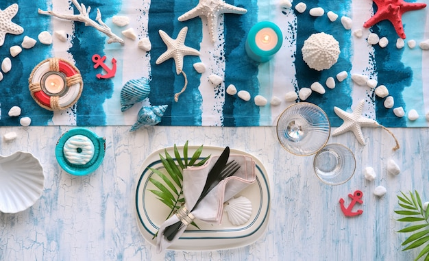 Contemporary summer table setting with nautical sea decorations on blue and white stripy runner Premium Photo