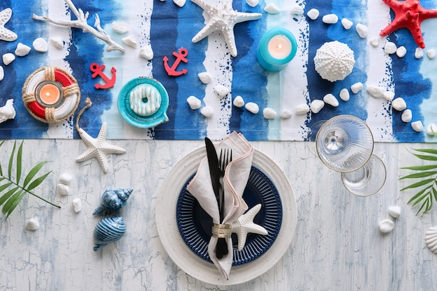 Contemporary summertime table setting with nautical sea decorations on blue and white stripy runner Premium Photo