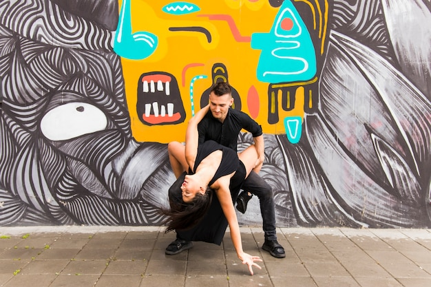 Contemporary urban street dancer dancing in front of graffiti Free Photo