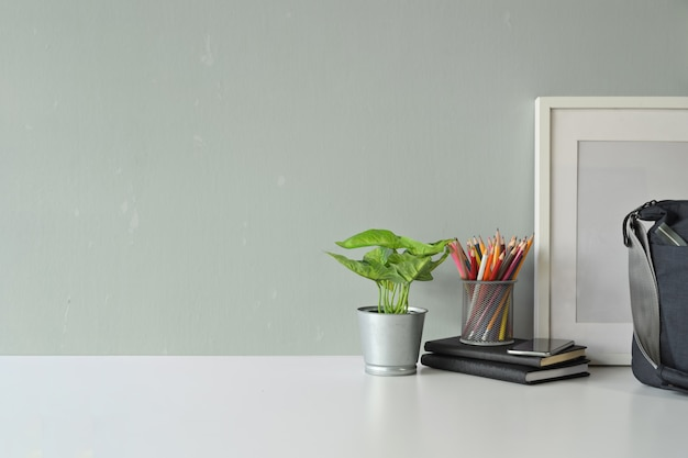 Contemporary workspace plant, mockup poster, bag and copy space. Premium Photo