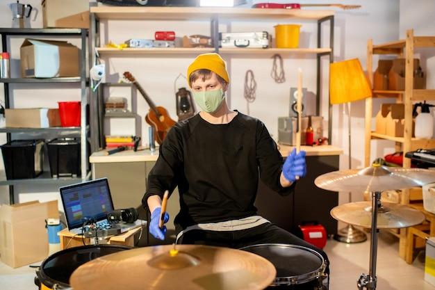 드럼 세트 앞에 앉아 새로운 음악을 만드는 동안 보호 장갑과 마스크를 들고 나지만 현대 젊은 남자 프리미엄 사진
