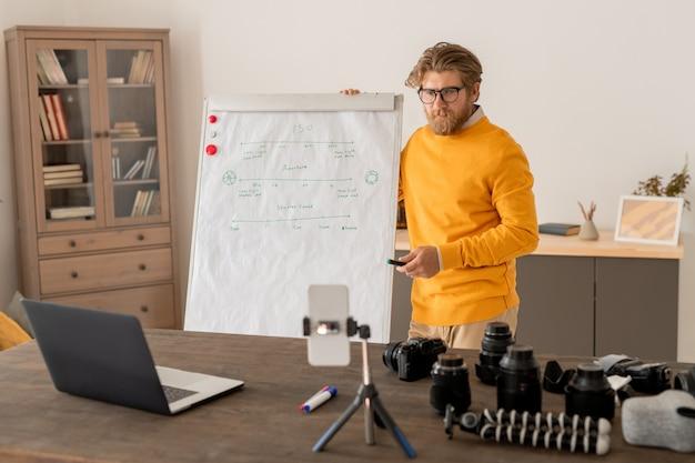 説明中にノートパソコンとスマートフォンのカメラの前にホワイトボードのそばに立っている蛍光ペンを持つ現代の若い教師 Premium写真