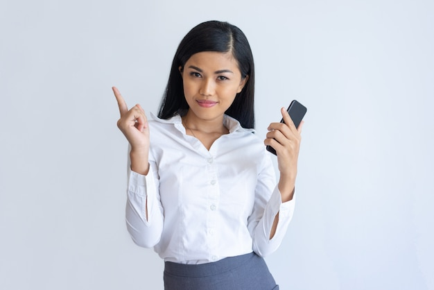 Content asian girl with phone having idea Free Photo