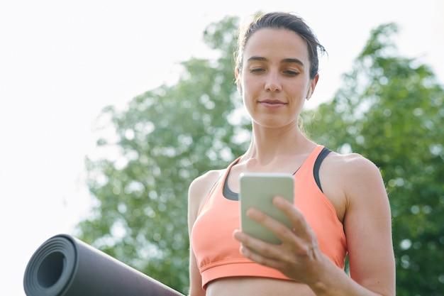 エクササイズマットを押しながら屋外で電話でヨガのエクササイズを見るスポーツブラで魅力的な女の子 Premium写真