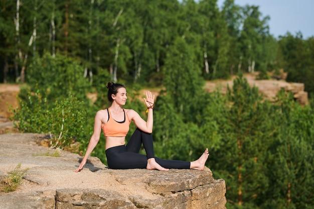 採石場の石の上に座って体を回転させながら、屋外で脊椎のコアを強化しながらスポーツウェアで美しい女性を満足させる Premium写真