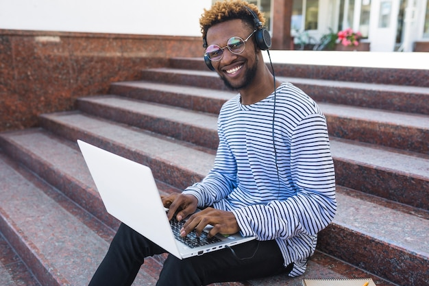 Content black man with laptop Free Photo