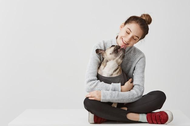 개 손에 들고 테이블에 앉아 캐주얼 옷에 콘텐츠 갈색 머리 아가씨. 그것은 그녀의 턱을 핥는 동안 혈통 강아지를 포옹 여성 시작 디자이너. 기쁨 개념, 복사 공간 무료 사진