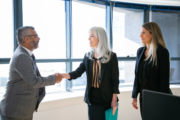 Content businesspeople greeting, meeting and smiling. successful indian ceo in eyeglasses handshaking with grey-haired businesswoman, talking and looking at her. business and partnership concept Free Photo
