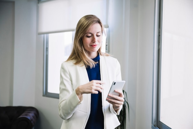 Content businesswoman looking at smarphone Free Photo