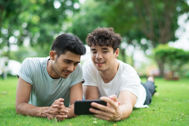Content couple of men posing for selfie on smartphone Free Photo