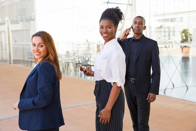 Content enterprising multi-ethnic business people in lobby Free Photo