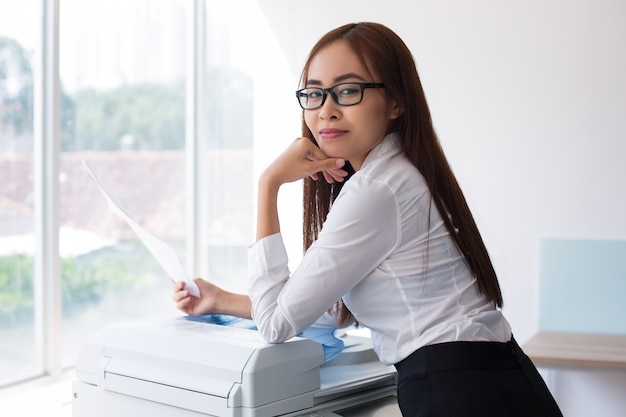 content female secretary with document at window photo free download