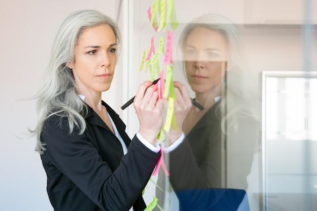 Donna di affari caucasica dai capelli grigi contenuto che scrive sull'adesivo con l'indicatore. responsabile femminile professionale concentrato che condivide l'idea per il progetto e che prende nota. Foto Gratuite