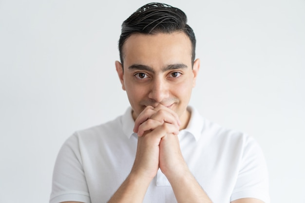 Content handsome man hoping for luck and holding hands together near mouth. Free Photo