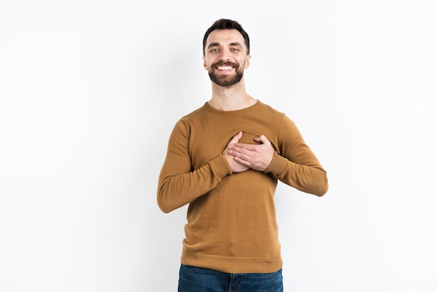 Content man posing while holding chest Free Photo