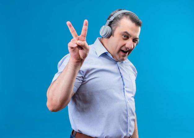 青い空間で2本の指を上げてカメラと手ジェスチャーを見るヘッドフォンで青い縞模様のシャツを着た中年男性 無料写真