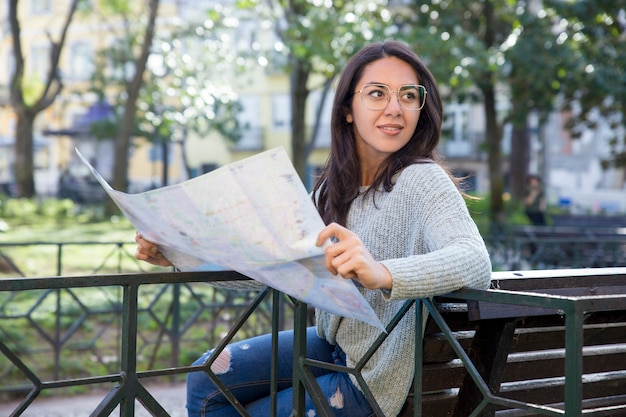 Content pretty young woman using paper map on bench outdoors Free Photo