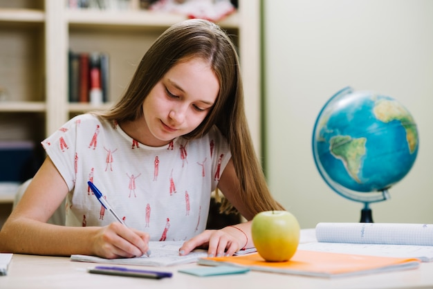 Content schoolgirl studying at table Free Photo