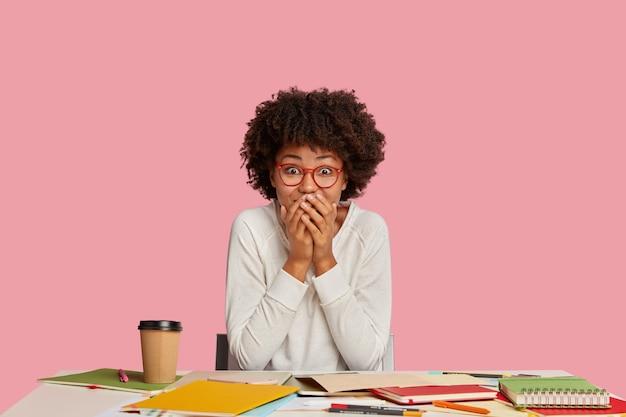 La donna di colore sorpresa del contenuto copre la bocca, guarda con gioia, non può credere nella promozione, ha reagito con piacere a qualcosa di positivo, si siede al desktop con il fermo. studenti felicissimi studiano al coperto Foto Gratuite