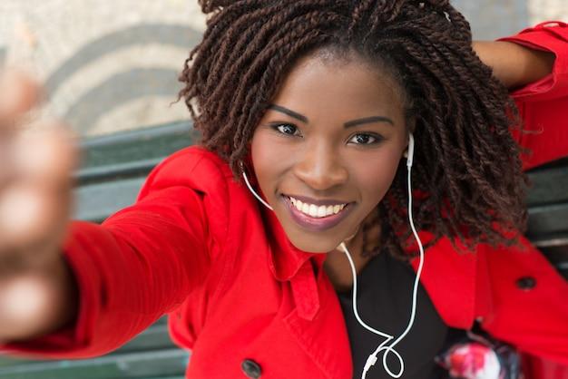 Content woman in earphones taking selfie Free Photo