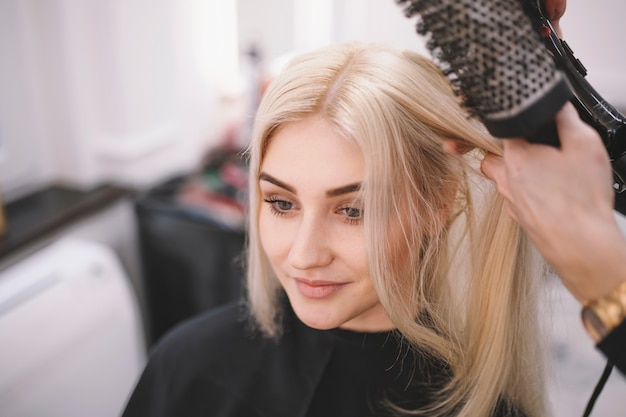 Content woman enjoying hair styling in salon Free Photo
