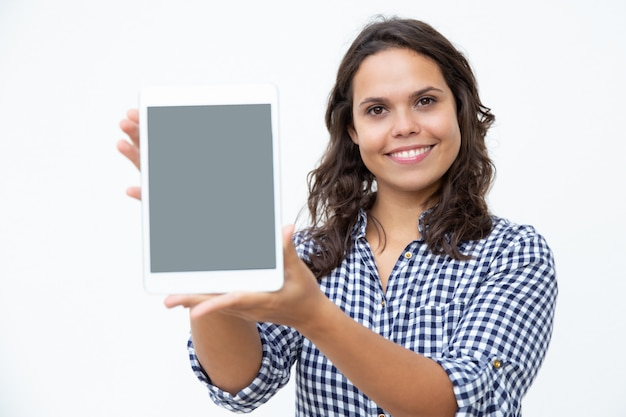 Content woman showing digital tablet Free Photo