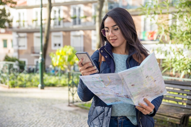 Content woman using paper map and smartphone outdoors Free Photo
