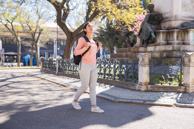 Content woman wearing backpack and walking around town Free Photo