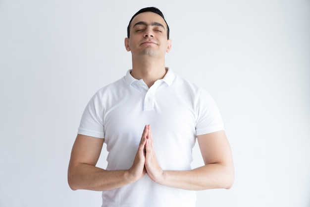 Content young man praying with his eyes closed and keeping hands together. Free Photo