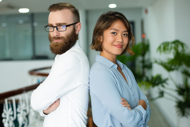 Content young multi-ethnic colleagues standing back to back Free Photo