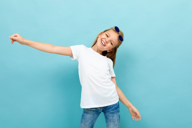 Contented charismatic girl schoolgirl in a white t-shirt on a blue background Premium Photo